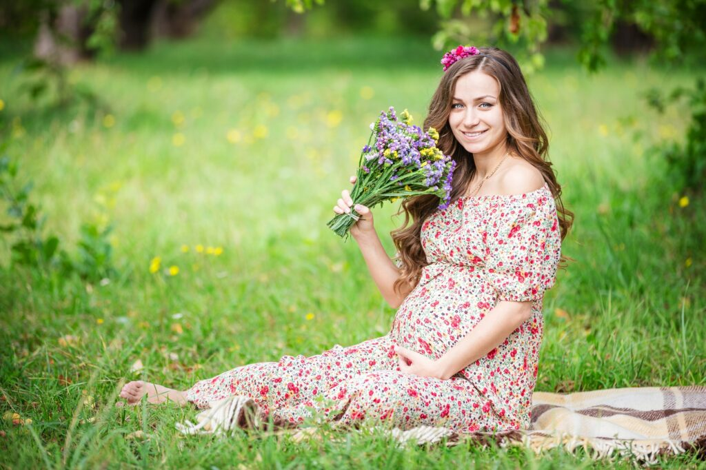 Beautiful pregnant woman holding flowers outdoors in summer park